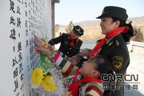 女干警正带领留守儿童朗诵记载先烈历史的碑文