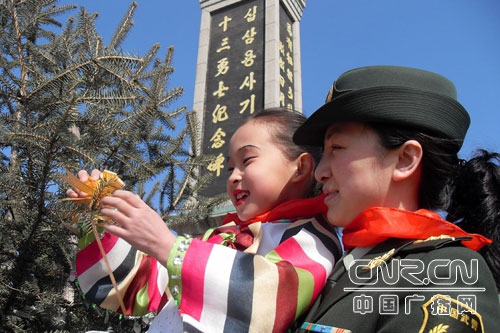 """4月2日,和龙大队的女干警与留守儿童来到和龙市烈士陵园,将一朵黄色纸花挂在""""十三勇士烈士纪念碑""""前的松树枝上。"""